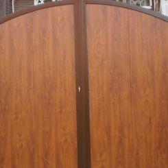 puerta-batiente-de-panel-imitacion-madera-y-acabado-en-curva-metalica